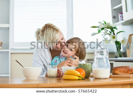 Mother and small daughter having breakfast in kitchen - stock photo