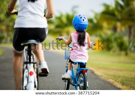 Mother and son are cycling in the park. - stock photo