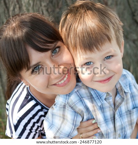 Mother and son are hugging and smiling - stock photo