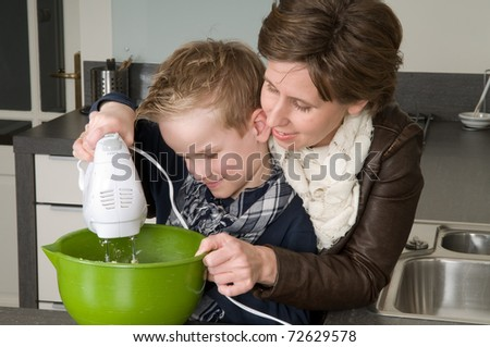 Mother and son are mixing the dough for the cake.