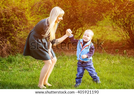 Mother and son are playing and having fun in the park in spring sunny day