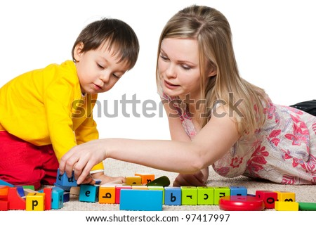 Mother and son are playing on the carpet with blocks - stock photo