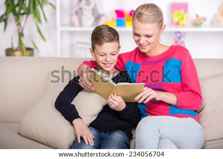 Mother and son are reading a book together. - stock photo