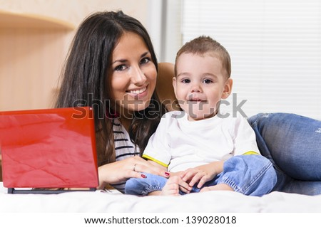mother and son are using laptop at home - stock photo