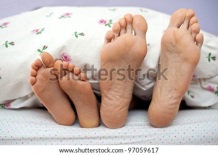 Mother and son bare feet in bed.