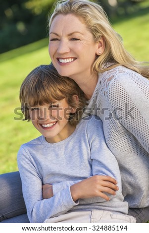 Mother and son, boy child and woman, laughing together, sitting outside in summer sunshine