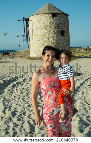 Mother and son boy on the beach with old windmill in background - stock photo
