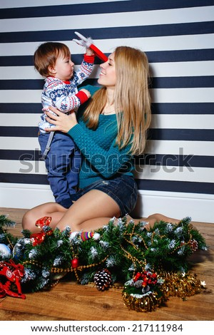 Mother and son cuddling in front of the Christmas tree at home - stock photo