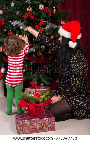 Mother and son decorate Christmas tree in their home