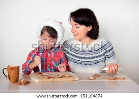mother and son decorating the gingerbread cookies