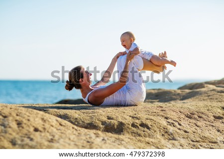 mother and son doing exercises on beach.
