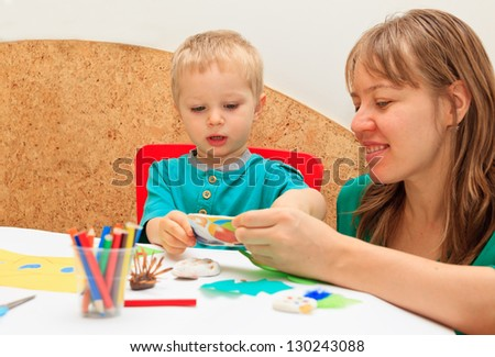 mother and son drawing together, good for kindergarten, daycare concepts - stock photo