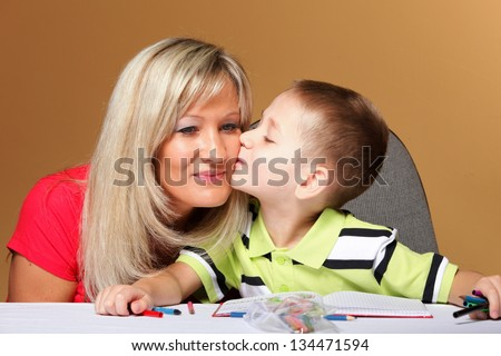 mother and son drawing together, helping with homework, child kissing mom on cheek, orange background - stock photo