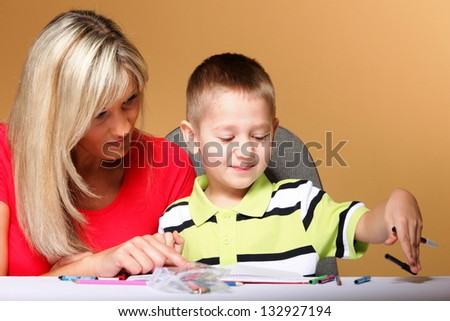 mother and son drawing together, mom helping with homework orange background - stock photo