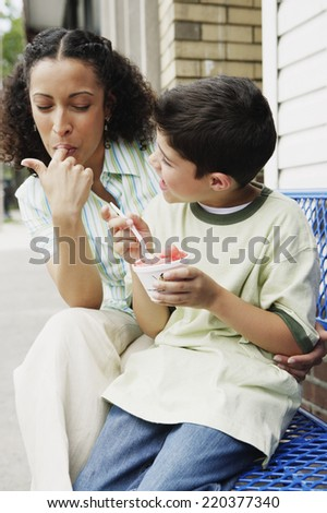 Mother and son eating ice cream together - stock photo