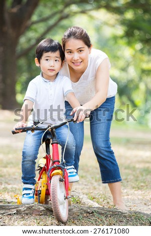 Mother and son enjoy activity together in the garden - stock photo