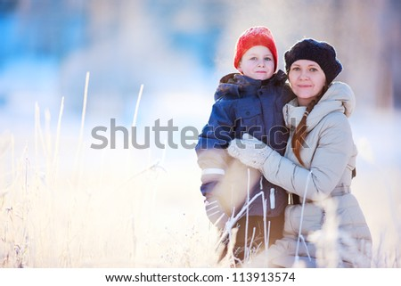 Mother and son enjoying beautiful cold winter day - stock photo
