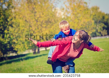 mother and son flying in autumn park, family fun