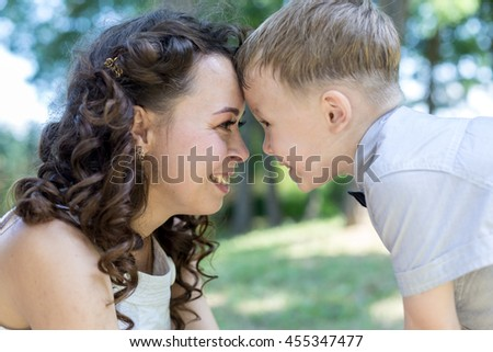Mother and son gently touch their foreheads to each other