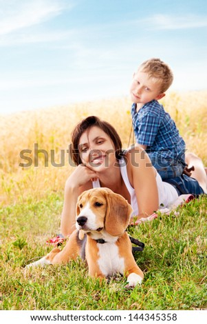 Mother and son have a nice leisure moment on the walk with his pet - stock photo