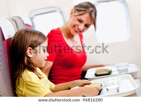 Mother and son having a meal in the airplane while flying - stock photo