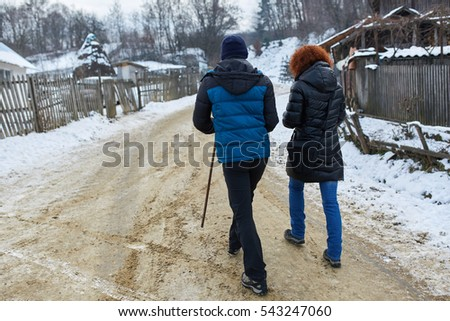 Mother and son having a walk through countryside in winter time
