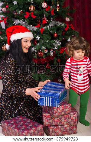 Mother and son having fun and opening Christmas presents