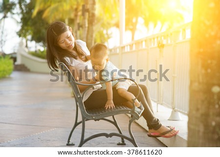 Mother and son having fun at outdoor in sunset during vacation. - stock photo