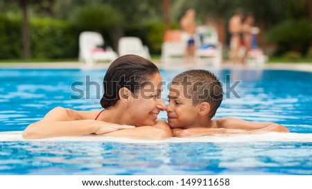 Mother and son having fun in swimming pool. - stock photo
