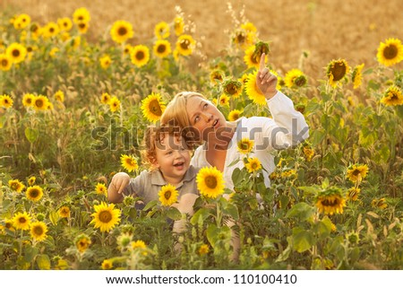 Mother and Son Having Fun in the field of sunflowers. Mother showing something to her son up in the sky. outdoor shot. - stock photo