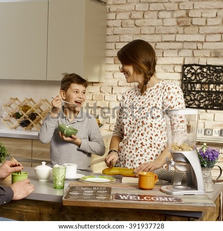 Mother and son having fun in the morning in the kitchen. - stock photo