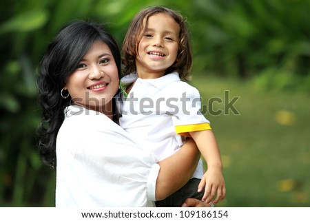 mother and son having fun in the park - stock photo