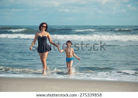 Mother and son having fun on a tropical beach during summer vacation - stock photo