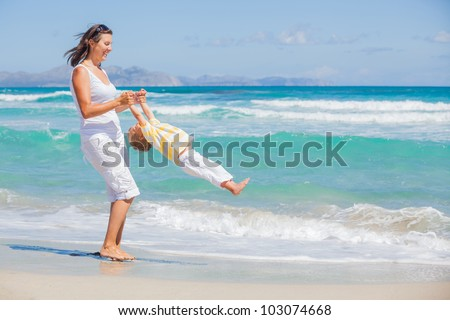 Mother and son having fun on tropical white sand beach