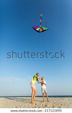 Mother and son having fun, playing with kite together. copy space - stock photo