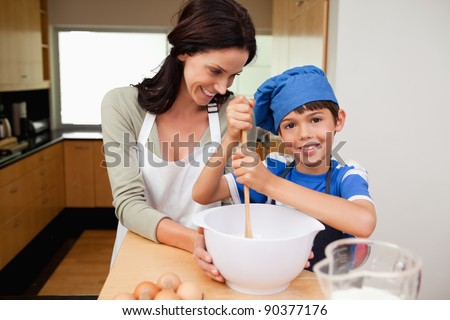 Mother and son having fun preparing a cake together