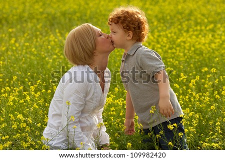 Mother and Son Having Fun. Son kissing his mother. outdoor shot. - stock photo