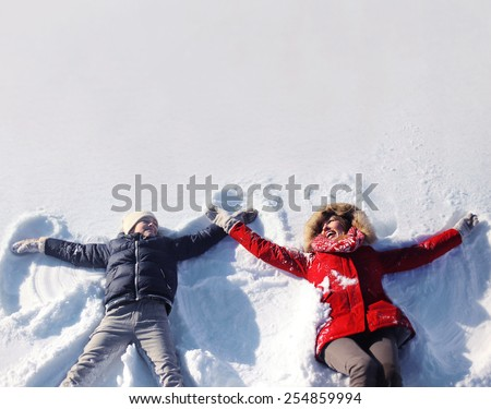 Mother and son having fun together lounging in the snow on a sunny winter day, copy space - stock photo