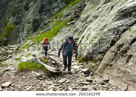 Mother and son hiking over rocky mountains on a trail - stock photo