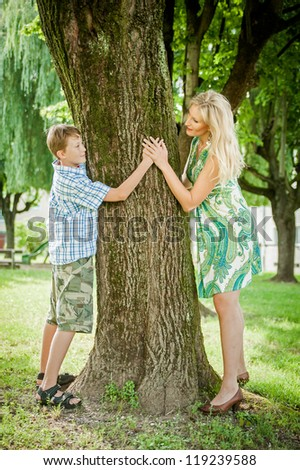 Mother and son holding hand around a tree - stock photo