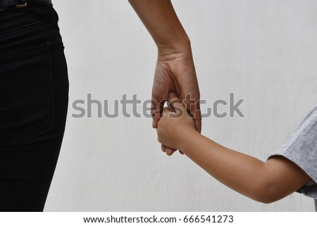Mother and son holding hands on wall background