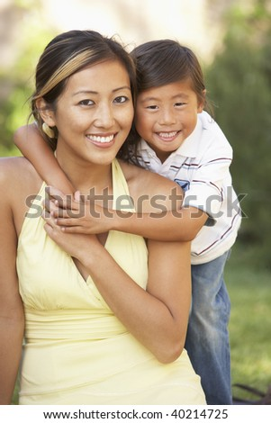 Mother And Son Hugging In Garden - stock photo