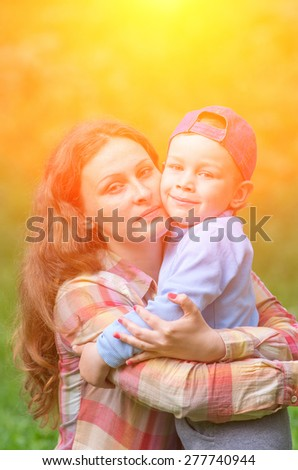Mother and son hugging in the street and look right. Family composition