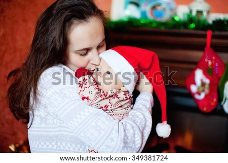 mother and son in a Christmas cap fireplace - stock photo