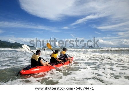 Mother and son in an ocean going kayak - stock photo