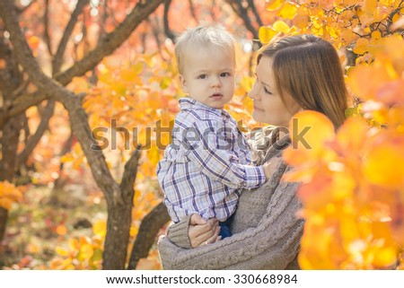 Mother and son in autumn forest