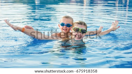 Mother and son in glasses for swimming swim in the pool.Family vacation.