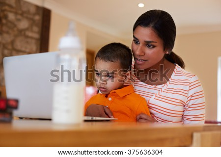 Mother And Son In Kitchen Looking At Laptop Together - stock photo