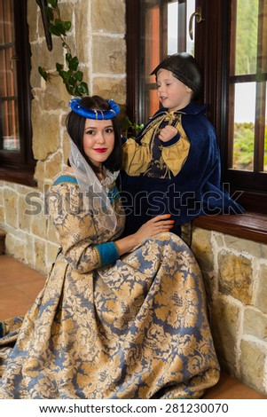 Mother and son in medieval costumes, in a beautiful interior. Costume photo session. - stock photo