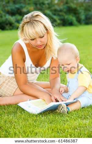 Mother and son in the backyard, reading - stock photo